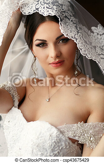 The tenderness bride stands in the room - csp43675429