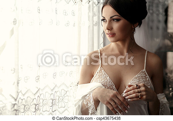 The tenderness bride stands near window - csp43675438