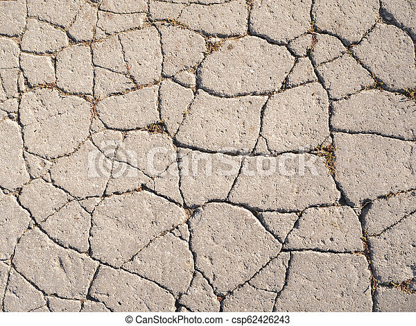 The texture of old asphalt with cracks. - csp62426243