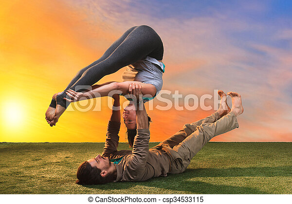 The two people doing yoga exercises  - csp34533115