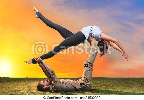 The two people doing yoga exercises  - csp34532923