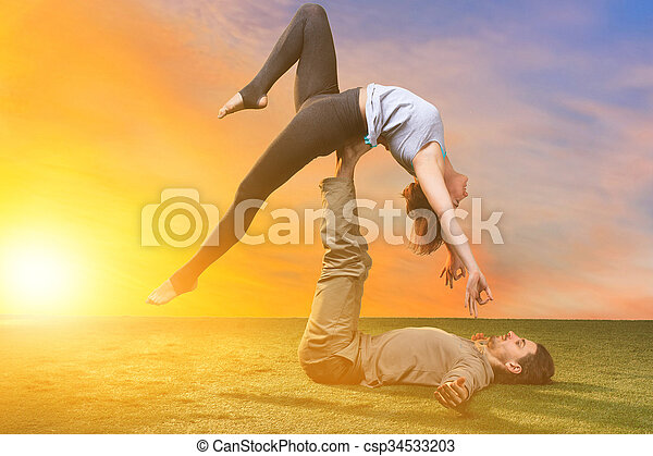 The two people doing yoga exercises  - csp34533203