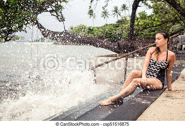 the woman sitting on the stairs by the sea - csp51516875