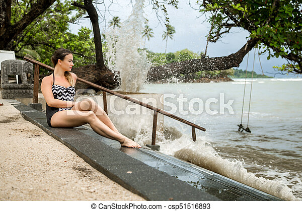 the woman sitting on the stairs by the sea - csp51516893