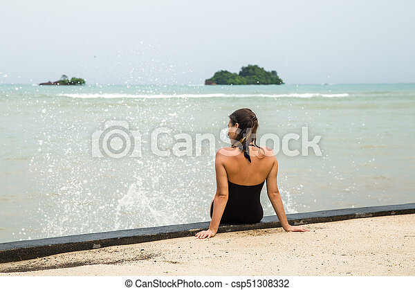 the woman sitting on the stairs by the sea - csp51308332