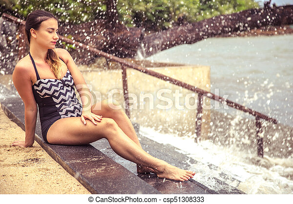 the woman sitting on the stairs by the sea - csp51308333