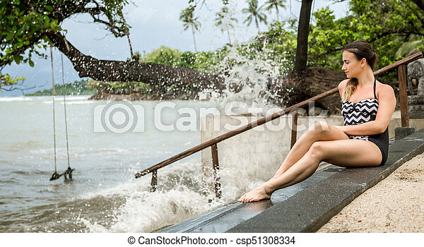 the woman sitting on the stairs by the sea - csp51308334