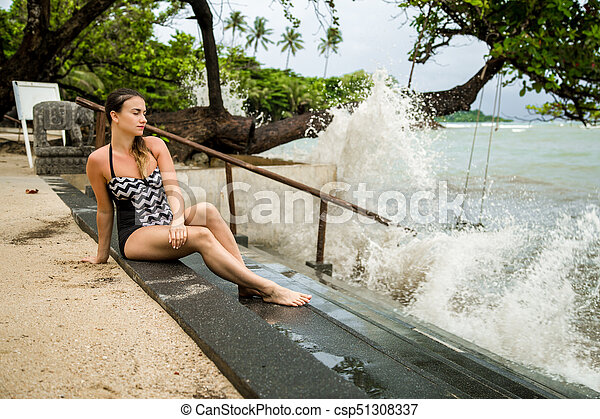 the woman sitting on the stairs by the sea - csp51308337