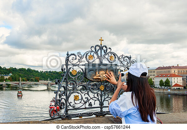 The woman touches the statue of St. John Nepomuk on Charles bridge Prague. The touch of a person to the memorial plaque of the Saint should bring good luck and ensure your well-being - csp57661244