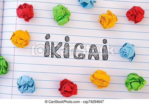 The word Ikigai on notebook sheet with some colorful crumpled paper balls around it - csp74294647