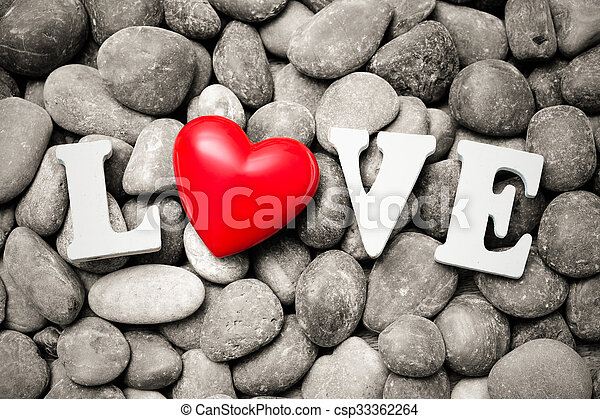 The word Love with red heart on pebble stones - csp33362264