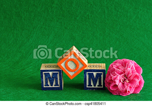 The word mom spelled with alphabet blocks against a green background with a pink flower - csp41805411