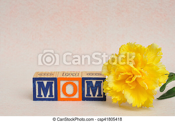 The word mom spelled with alphabet blocks against a white background with a yellow flower - csp41805418
