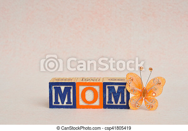 The word mom spelled with alphabet blocks against a white background and a silk butterfly - csp41805419