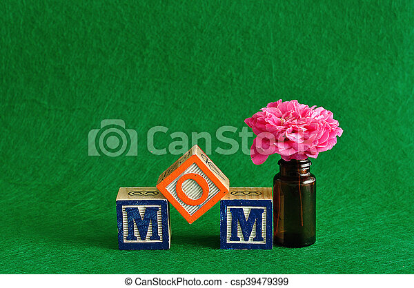 The word mom spelled with alphabet blocks against a green background with a pink flower - csp39479399