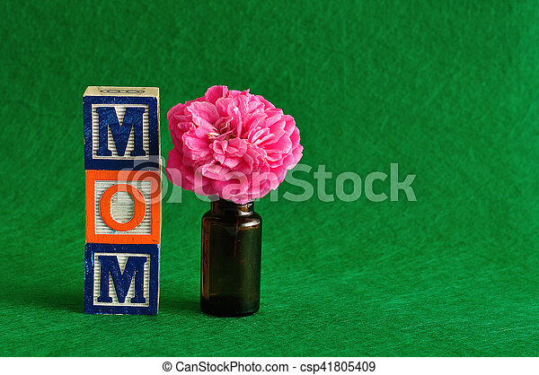The word mom spelled with alphabet blocks against a green background with a pink flower - csp41805409