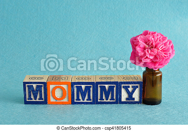 The word mommy spelled with alphabet blocks against a blue background with a pink flower - csp41805415
