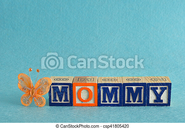 The word mommy spelled with alphabet blocks against a blue background and a silk butterfly - csp41805420