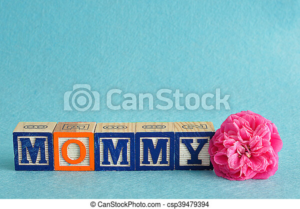 The word mommy spelled with alphabet blocks against a blue background with a pink flower - csp39479394