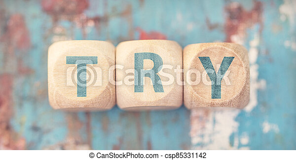 The word try on wooden cubes - csp85331142