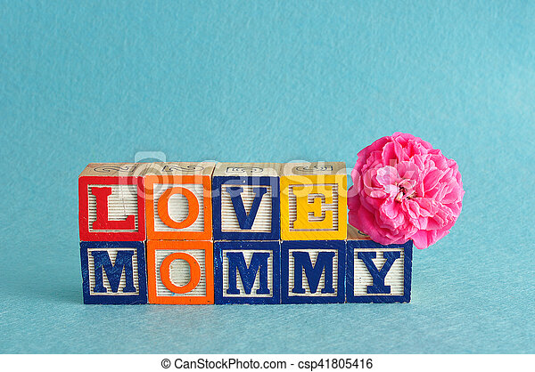 The words love mommy spelled with alphabet blocks against a blue background with a pink flower - csp41805416