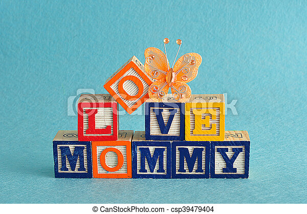 The words love mommy spelled with alphabet blocks against a blue background with a orange butterfly - csp39479404