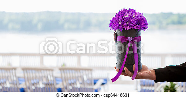 The young man gives a bunch of purple chrysanthemums. - csp64418631