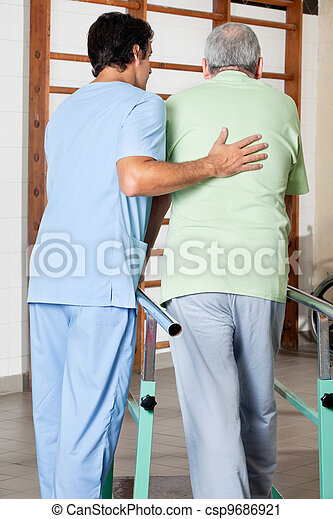 Therapist Assisting Senior Man To Walk With The Support Of Bars - csp9686921