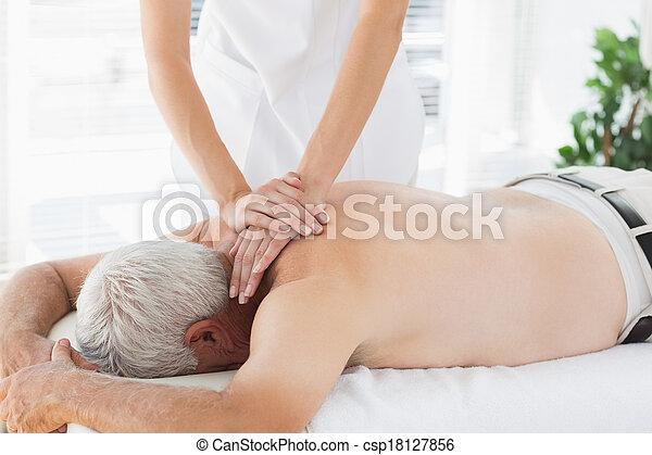 Therapist massaging back of senior patient - csp18127856