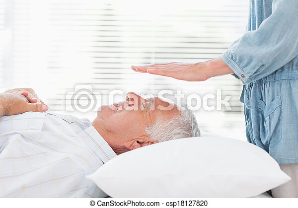 Therapist performing Reiki over senior man - csp18127820
