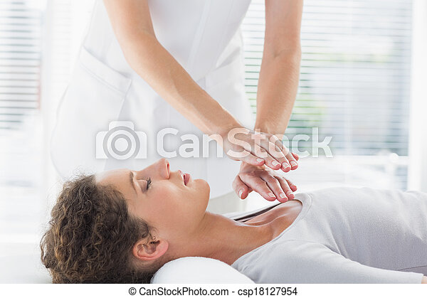 Therapist performing Reiki over wom - csp18127954