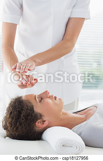Therapist performing Reiki over woman - csp18127956