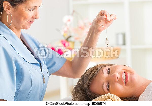Therapist using pendulum - csp19065874