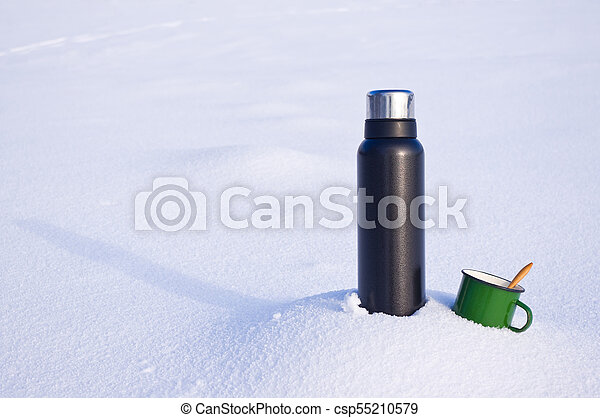 Thermos and mug in the snow - csp55210579