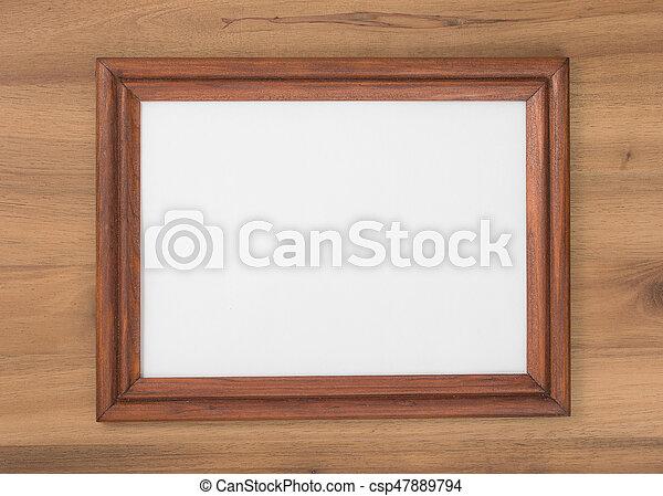 Thin wooden frame on a wood board surface, dark brown rectangular ...