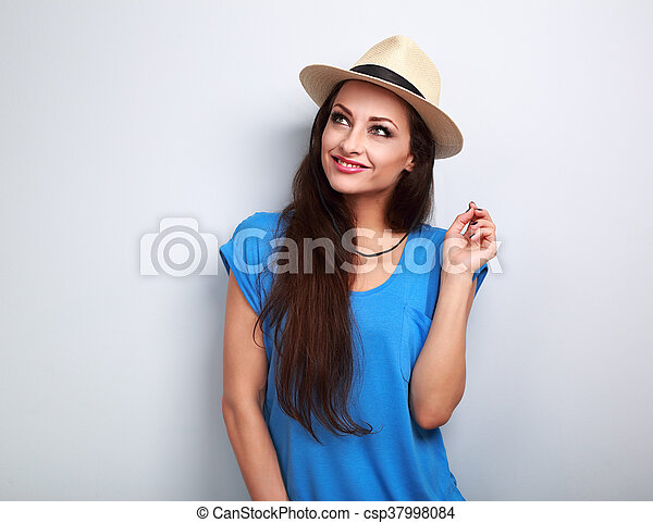 Thinking beautiful woman in hat and blue top looking up on blue background - csp37998084