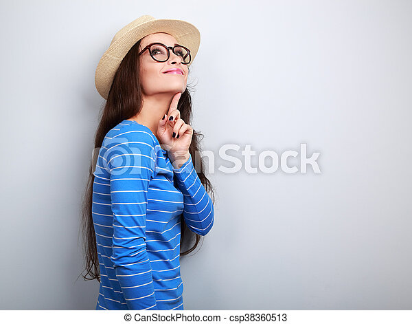 Thinking young happy woman in hat and glasses looking up on blue background - csp38360513
