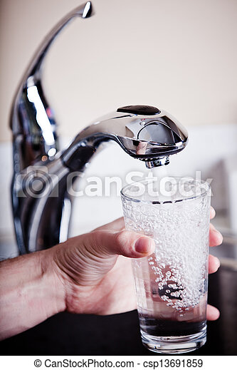 Thirsty man filling a big glass of water - csp13691859