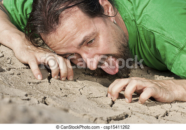 Thirsty man on parched soil - csp15411262