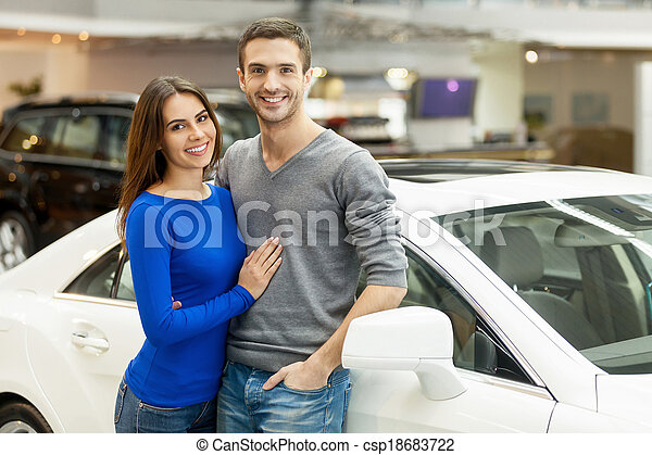 This car is exactly what we want. Beautiful young couple standing at the car dealership and making their decision - csp18683722
