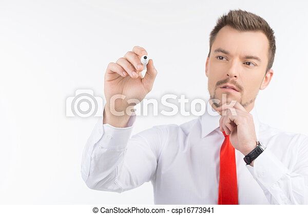 Thoughtful businessman. Confident young men writing something on transparent whiteboard while standing isolated on black - csp16773941