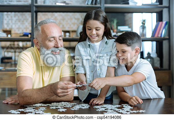 Thoughtful elderly man and grandchildren putting puzzle together - csp54194086