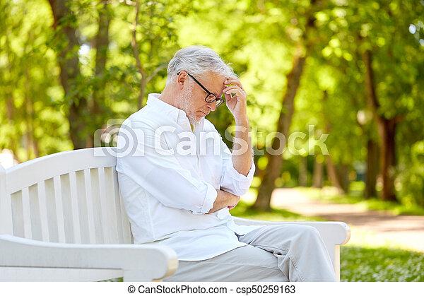 84518aa1e7b89 thoughtful senior man sitting at summer park - csp50259163