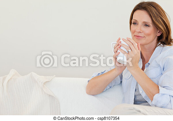 Thoughtful woman with cup of coffee on sofa - csp8107354