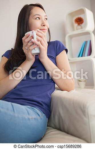 Thoughtful young asian woman sitting on the couch holding mug - csp15689286