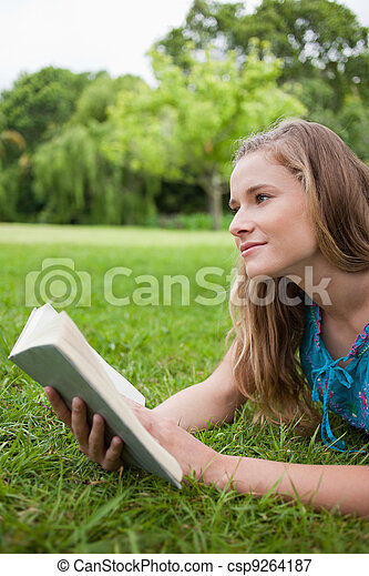 Thoughtful young woman holding a book while looking away - csp9264187