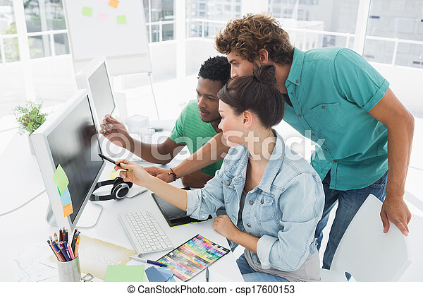 Three artists working on computer at office - csp17600153
