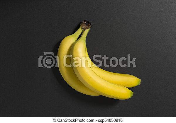 Three bananas on a black background. - csp54850918