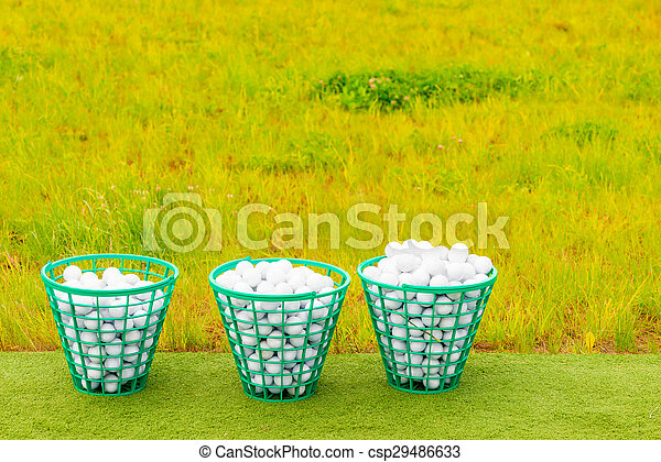 three baskets filled with golf balls on the green grass - csp29486633