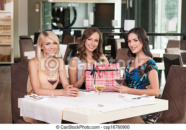 Three Beautiful Woman Sitting At The Restaurant Having Birthday Present On Table